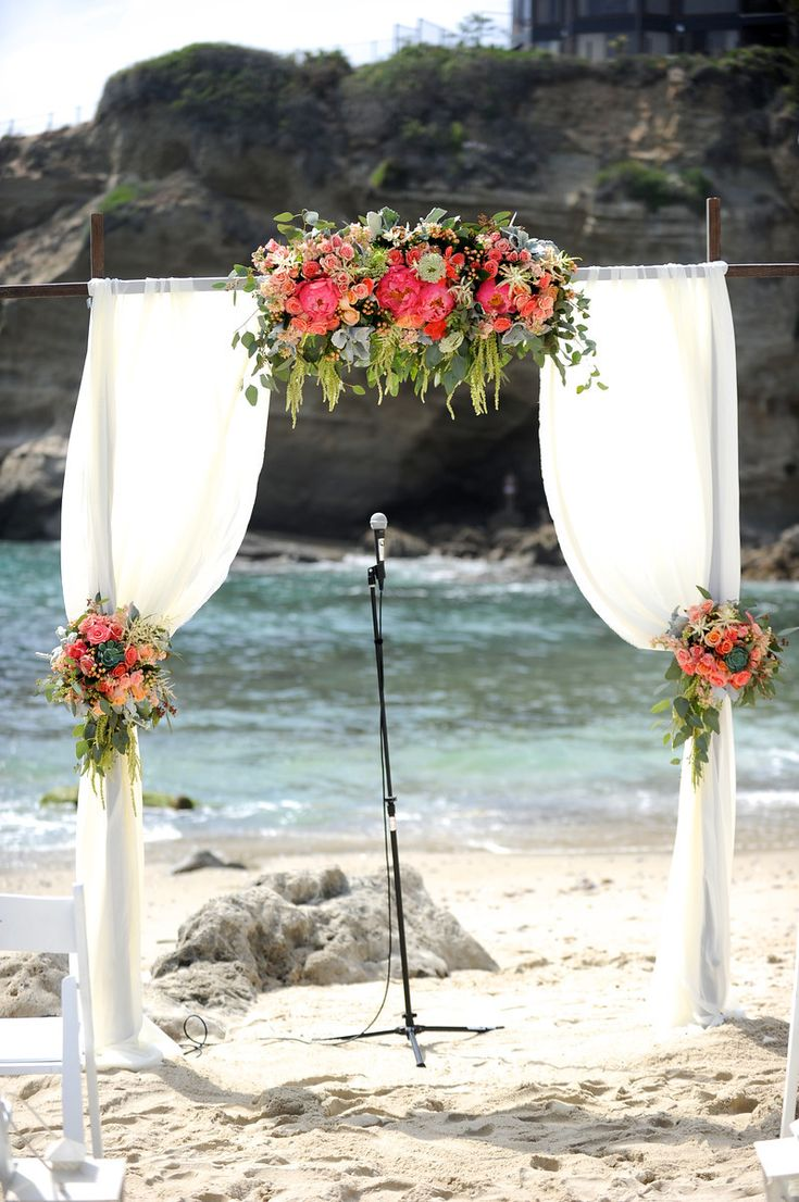 Wood wedding arch with draping fabric and flowers. Coral, peach, ivory, green. Beach wedding. Coral peonies, roses, amaranthus, succulents, astilbe, dusty miller. Florals by Jenny// Images © Gavin Wade Photographers - www.gavinwadephoto.com