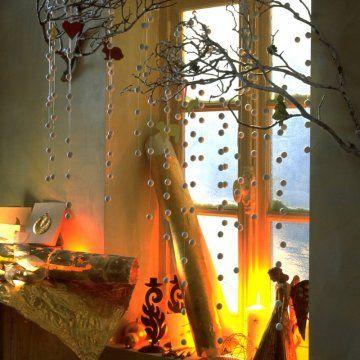 rideau de boules de coton blanc accroché à deux branches au-dessus d'une fenêtre