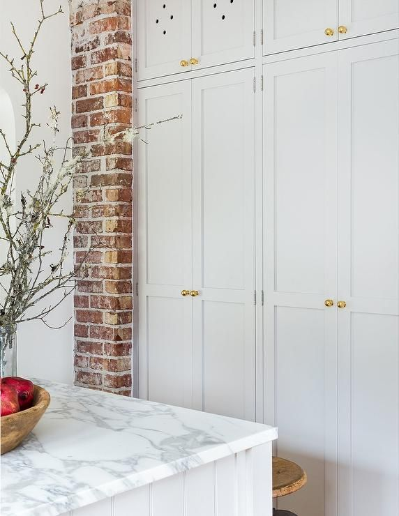 Exposed Brick Frames Floor To Ceiling White Shaker Kitchen Cabinets Accented With Antique Br Shaker Doors Kitchen Cabinets To Ceiling Floor To Ceiling Cabinets