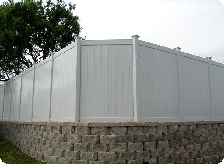 Vinyl privacy fence on a retainer wall http gateforless for Decorative wall fence