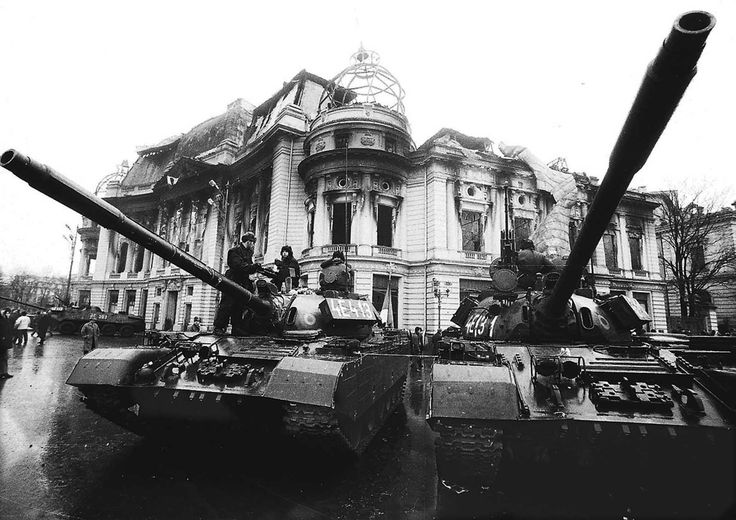 Tanks in front of a burned government building.