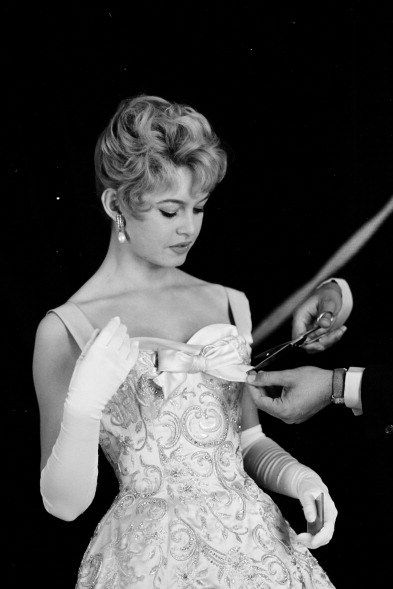 Brigitte during a fitting for her Balmain gown to meet Queen Elizabeth II in 1956.