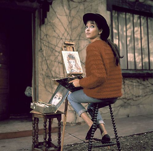 Anna Karina, better than Audrey.  Rolled slim jeans, big cropped sweater.  (Bonus: hilarious Precious Moments style painting on easel.)