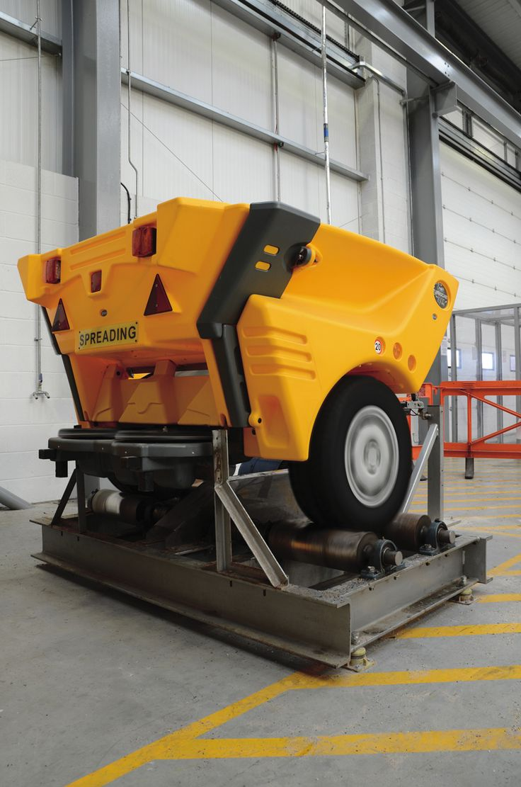 The Turbocast 1000™ towable salt/grit spreader being tested on a rolling road.  The Turbocast 1000 is a large capacity towable gritter that can be used as a drop or broadcast spreader.