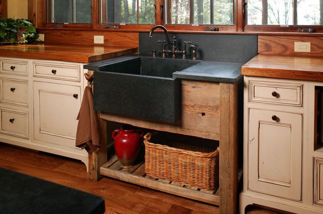 This Rustic Kitchen Has A Stand Alone Farmhouse Apron Sink In Black Stone Sitting On A Wooden Base Rustic Kitchen Sinks Rustic Kitchen Cabinets Rustic Kitchen