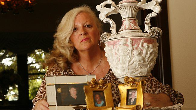 """Gangland widow and killer Judy Moran with photos of deceased sons Mark and Jason, and the urn of Lewis Moran. Mrs Moran is currently serving a 26-year prison sentence for her role in the murder of her brother-in-law, Desmond """"Tuppence"""" Moran. Picture: Alex Coppel Source: AdelaideNow"""