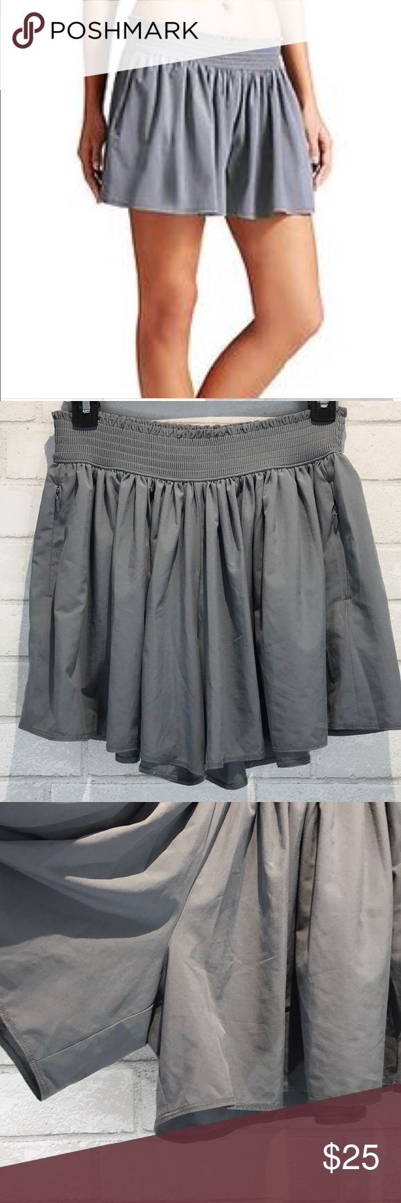 """Athleta Flowy Gray Athletic Sneaky Shorts This is a pair of Athletic Sneaky Shorts in a size XS. These shorts are flowy and almost appear like a skirt with pockets on each side. The shorts are in excellent used condition with no flaws. The total length measures 14"""" and there is an adjustable elastic waist. Thanks! Athleta Shorts"""