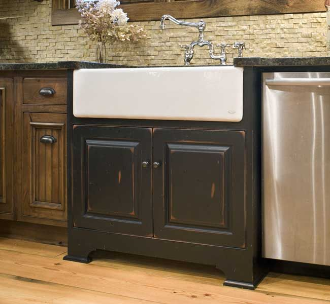 A white farmhouse sink with black sink base cabinet and ...