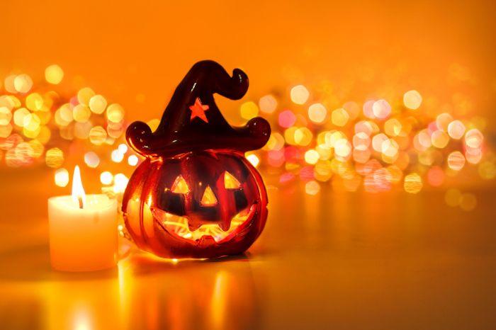 eine Figur aus Glas neben einer Kerze und glänzende Lichter im Hintergrund   Halloween Hintergrund