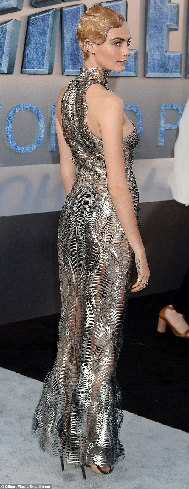 Model figure: The patterned metallic-looking dress molded itself to the British actress's body  and a split at the front showed off her lean legs