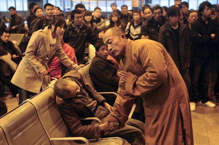 一名老人在火车站候车室去世,一名正在等车的僧人上前握住死者的手进行超度。