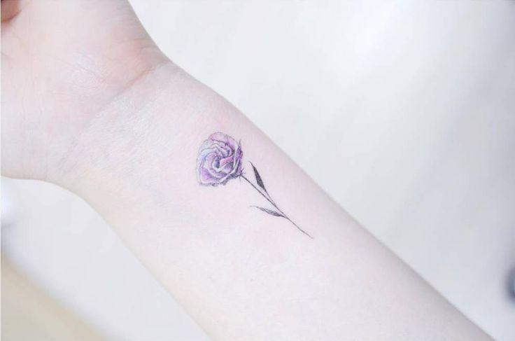 Illustrative lisianthus flower tattoo on the left inner wrist.