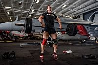 Lt. Joshua Johnson lifts weights in the hangar bay of the aircraft carrier USS Theodore Roosevelt (CVN 71).  Theodore Roosevelt and its carrier strike group are deployed to the U.S. 5th Fleet area of operations in support of maritime security operations to reassure allies and partners and...