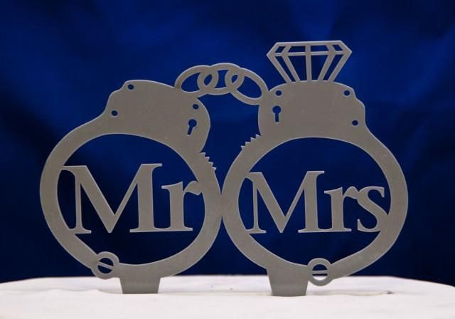 This Mr. and Mrs. handcuffs cake topper is made from food safe acrylic and we have many colors to choose from. This cake topper is 5.5 inches wide and stands 3.75 inches tall not including the spikes attached to the bottom. The spikes are permanently attached to the cake topper and cannot be removed. The colors we have available are Black, White, Ivory, Royal Blue, Chocolate Brown, Red, Green, Yellow, Purple, Clear, Translucent Gray and Gray.Please leave us a note with your purchase…