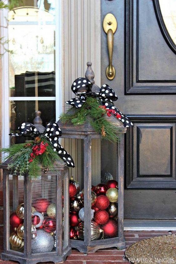 Fill wooden lanterns with Christmas ornaments and decorate with ribbon and Christmas greenery for a beautiful handmade look for the holidays.