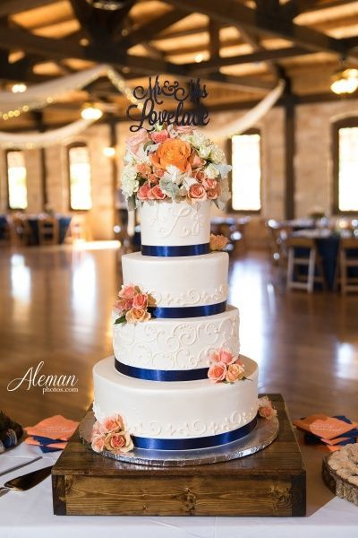 White, four-tier, round wedding cake for a navy blue, pink, and orange wedding!
