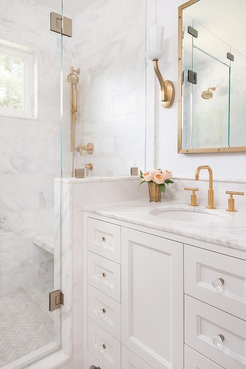 White And Gold Bathroom Features A White Washstand Adorned With Glass Knobs  Topped With White Marble