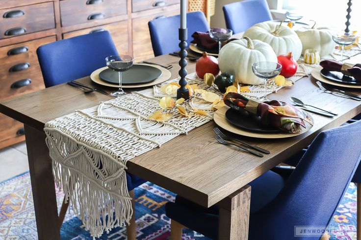 Decorate your dining room for Fall with this vibrant and eclectic table setting featuring matte black dinnerware, pumpkins, plums, and pomegranates.