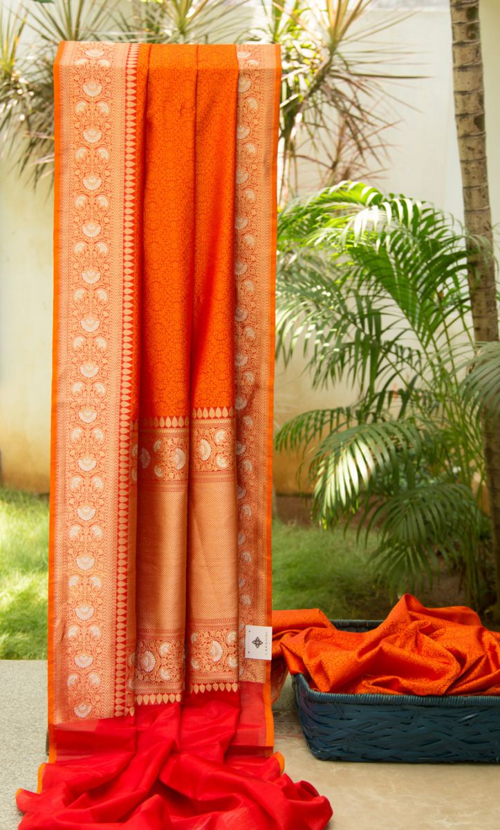 Red and Orange tanchoi benares silk. The saree is finished beautifully by the intricately woven gold work on the pallu and the border