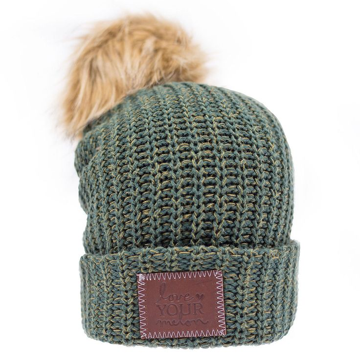 This pom beanie is knit out of 100% cotton yarn in hunter green and olive colors. It features a brown leather patch that is debossed with the Love Your Melon logo and a detachable, natural faux fur po