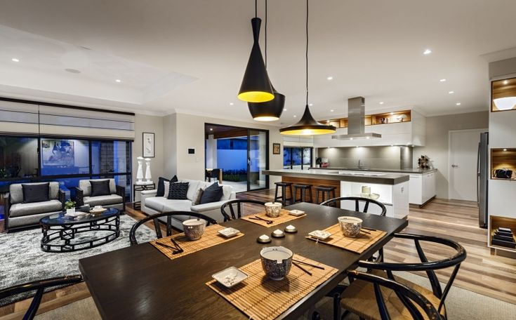 Although this great room has an absent vaulted ceiling, it still combines the formal living room with an adjacent kitchen and dining area. Each space is designated separate via an area rug.