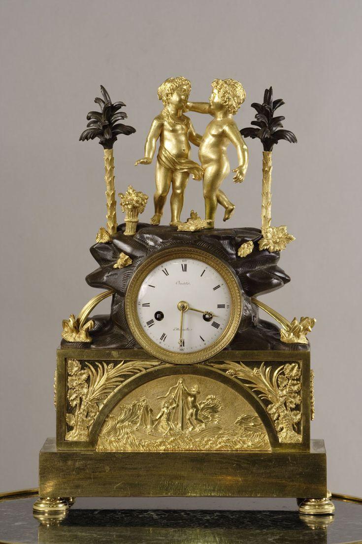 Pendule en bronze doré et patiné représentant l'histoire de Paul et Virginie, dans un cadre exotique avec deux palmiers. Circa : 1790.