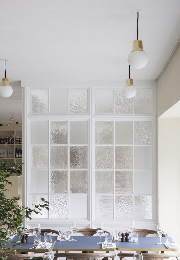 Great way to add interest and separation in a room a wall of window panes filled with different patterned opaque glass.