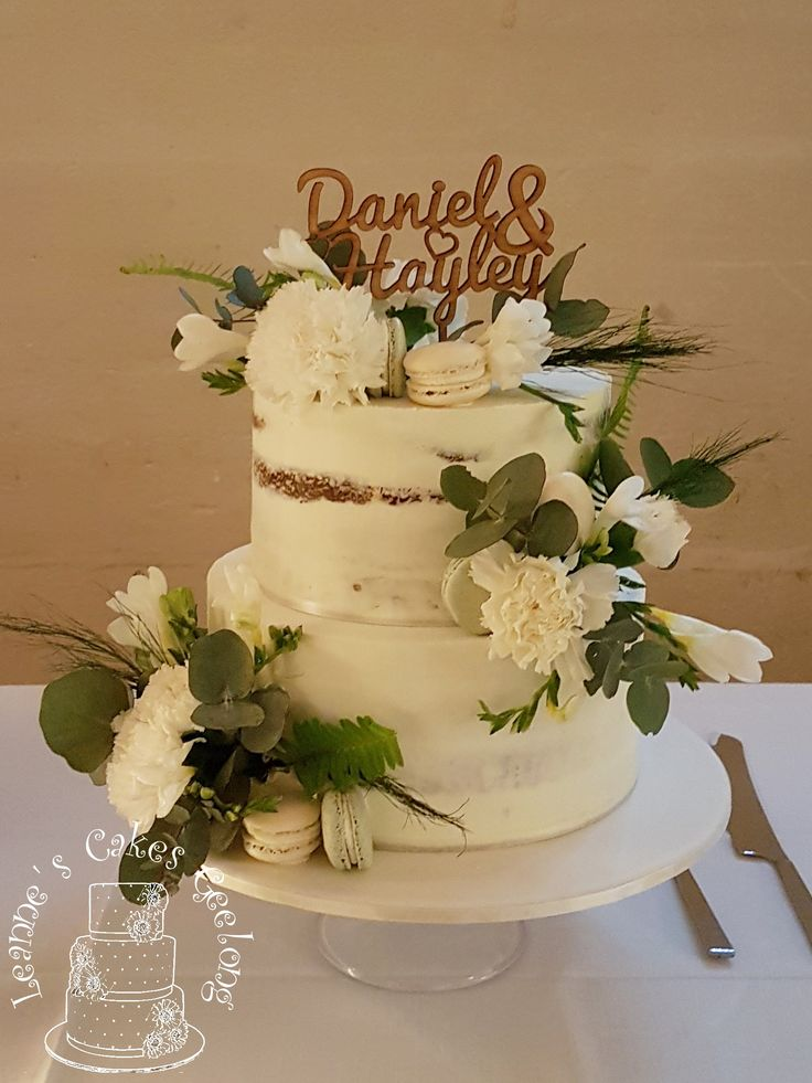 Daniel and Hayley celebrated their engagement with this semi-naked cake decorated in greenery and white including home made macarons. Top tier is caramel mud cake and bottom tier is vanilla mud cake. They are filled and covered in white chocolate buttercream. www.facebook.com/cakesbyleannerhodes