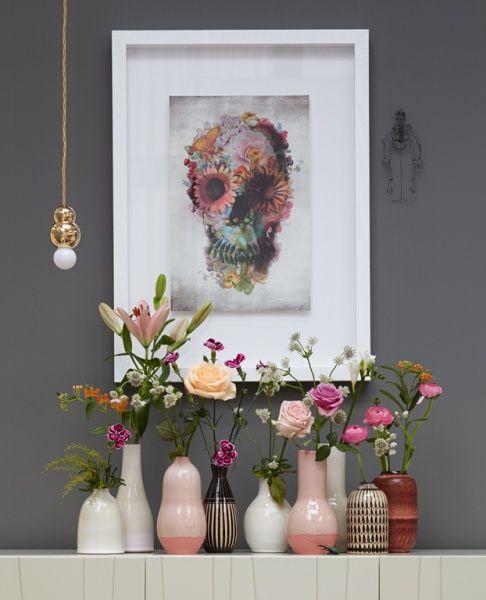 Mooie combi met de grijze achterwand en de poedertinten in vazen en bloemen.