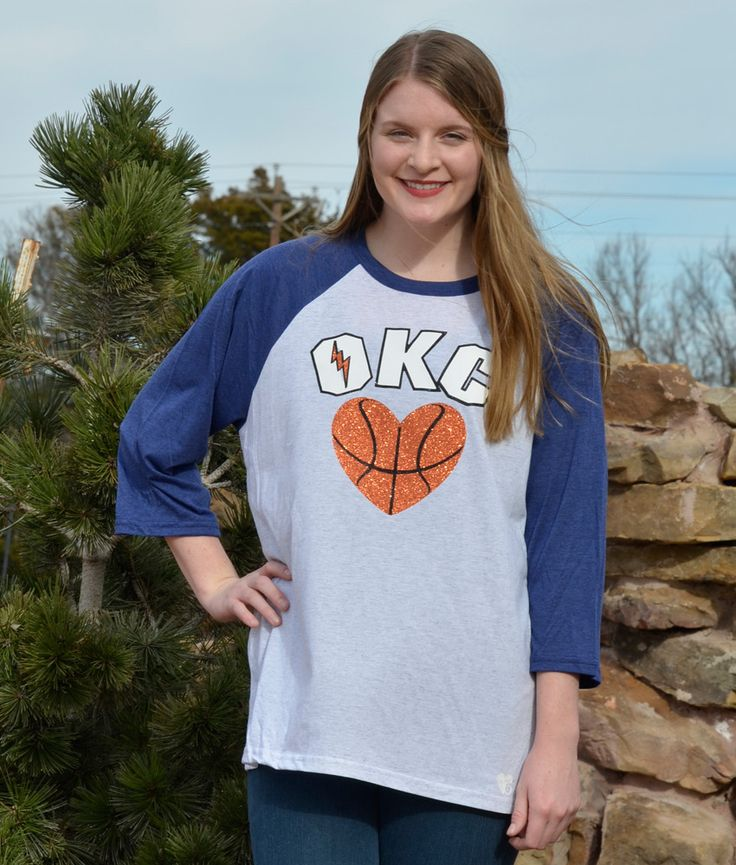 OKC Basketball Shirt Basketball fans will sparkle in this OKC heart basketball shirt! Lettering, thunder bolt and basketball are glitter. Made on a soft and comfortable raglan white fleck and navy shi