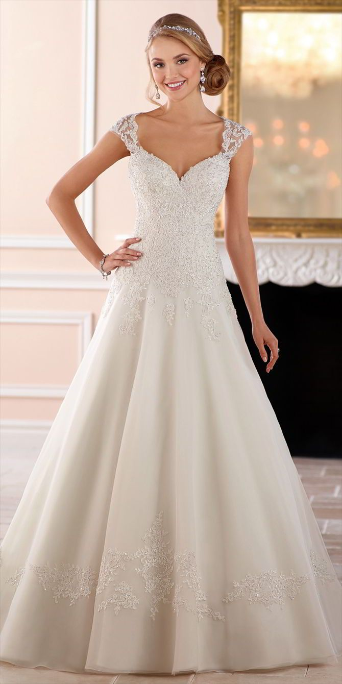 This keyhole back princess wedding dress from Stella York is a traditional bride's dream gown! Lace and tulle over Royal organza in a modified A-line silhouette creates a magical moment when twinkling beading is added, giving an extra pop of glamour. A lace detail surrounds the skirt just above the hem, mirroring the lace edges of the sparkling bodice. Wide straps come across the back, forming an elegant keyhole back.