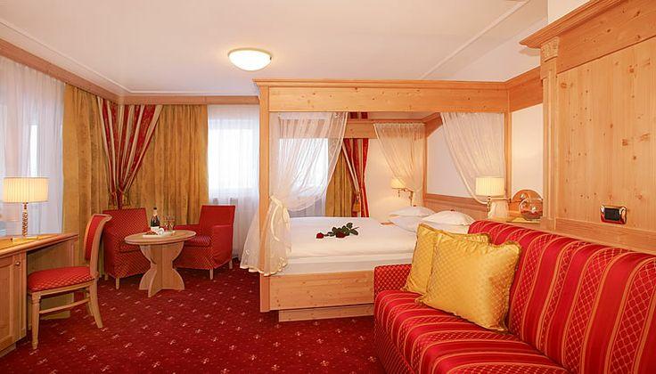 Una habitación doble con una cama doble y medio, con el pabellón (acabada en madera).Hay una alfombra roja, como el sofá al lado de la cama,y un escritorio con  una silla.