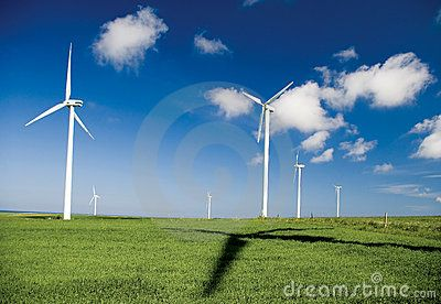 #windturbine #windturbines in northern Poland. Shadow cast in the foreground grass. Clear blue sky. Green energy concept.
