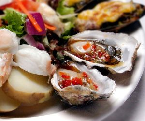 Grilled oysters with ginger dressing.Grilled oysters with soy sauce and ginger.