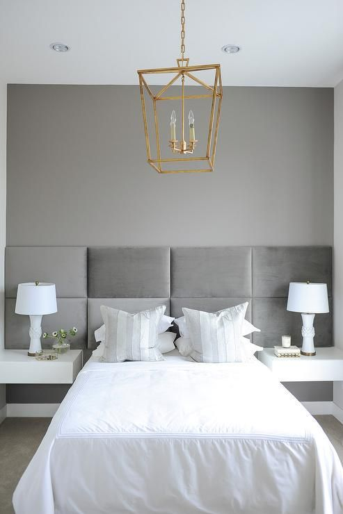 White and gray bedroom features a full length gray padded headboard mounted on wall lined with a bed dressed in white bedding as well as gray and silver striped pillows flanked by white floating nightstands illuminated by an antique brass lanterns, Darlana 4 Light Lantern.