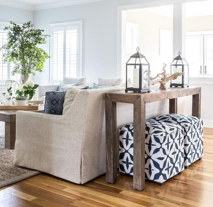 White and blue cube poufs sit under a brown sofa table topped with iron and glass candle lanterns and positioned behind an ivory linen sofa accented with blue pillows. #coastallivingroomsbrowncouch