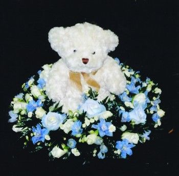 Teddy on Posy Pad - http://libertyflowers.co.uk/funeral-flowers/teddy-on-posy-pad?___SID=U