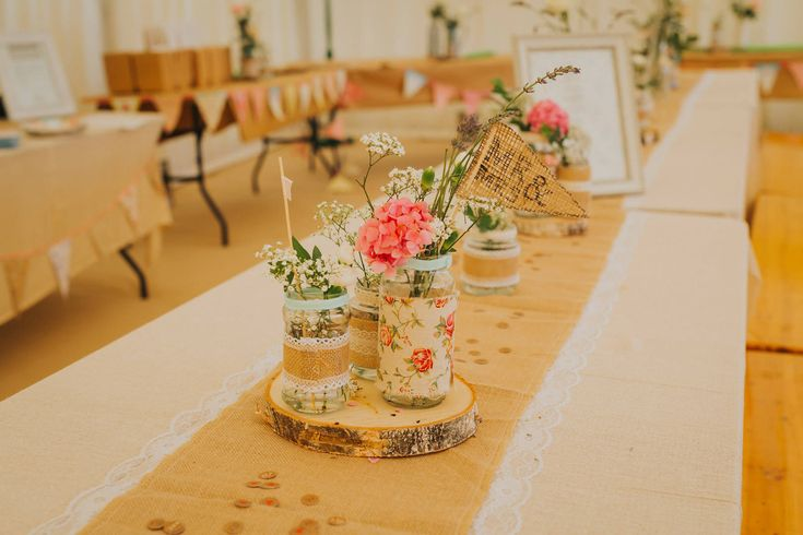 Beautiful jars full of fresh flowers are perfect for the centre of your dining tables. Photo by Benjamin Stuart Photography #weddingphotography #tablecentres #jamjarflowers #DIYwedding #festivalwedding #banquettable #weddingdecor #receptiondecor