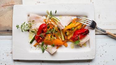 Ein Teller Gemüsepfanne mit Putenbrust steht auf dem Tisch.