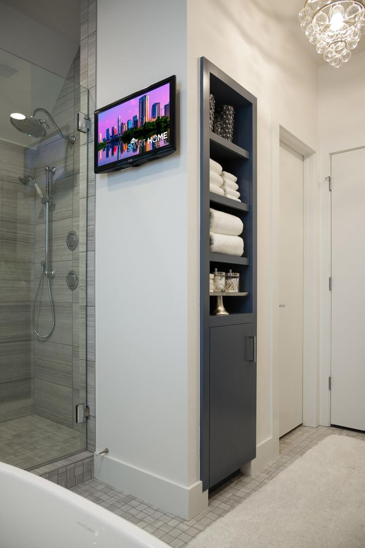Built-in shelves in a rich, deep blue are a space-saving storage solution. Did we mention you can see the TV from the soaking tub?? --> http://www.hgtv.com/design/hgtv-smart-home/2015/master-bathroom-pictures-from-hgtv-smart-home-2015-pictures?soc=smartpin