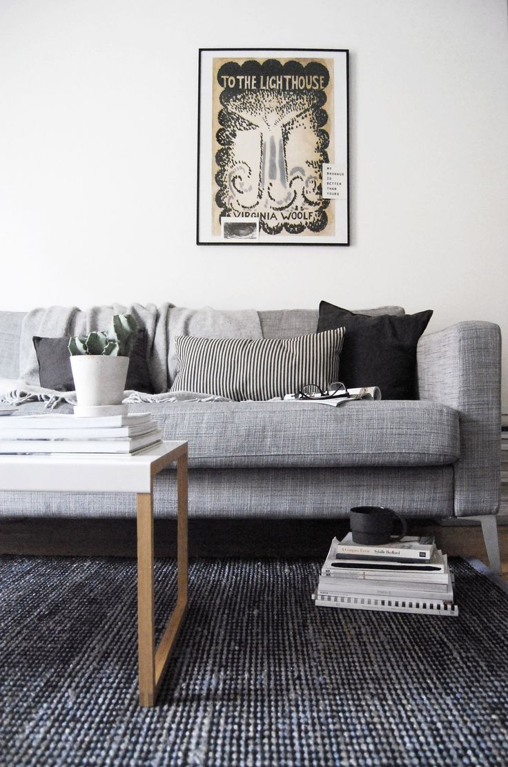 A Moody Monochrome Living Room With White Walls Grey Sofa And Dark Rug