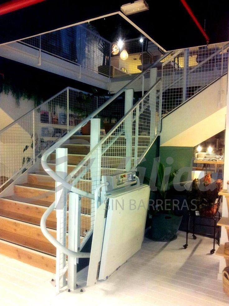DÉCOR plataforma salvaescaleras instalada en el interior de una local comercial de Barcelona por Válida sin barreras. Vista de la plataforma plegada en la planta inferior. Tramos con curvas y terminación en s.