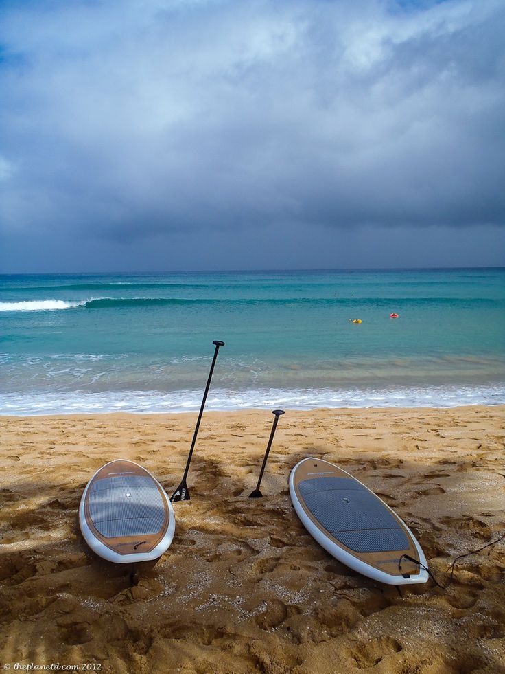 Stand up paddle boards on beach | The Planet D: Adventure Travel Blog