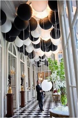 Using balloons to create a focal point at your party is extremely cost effective. These black and white ones look brilliant to dress the hall way.