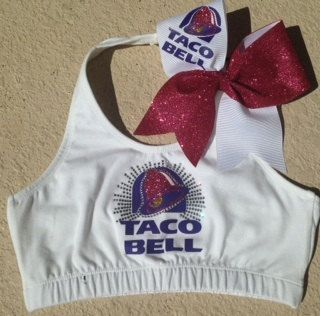 This is a WHITE HALTER top sports bra with TACO BELL on it. It is designed with purple, hot pink, and gold glitter vinyl. The bow is