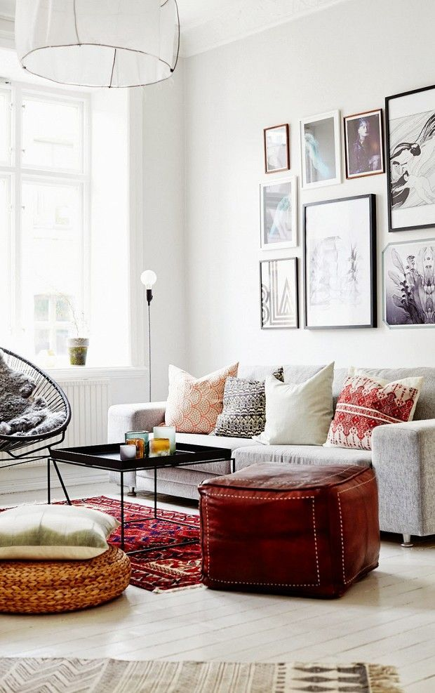 living room poufs%0A Living room with gallery wall of framed art  patterned throw pillows  and  leather pouf