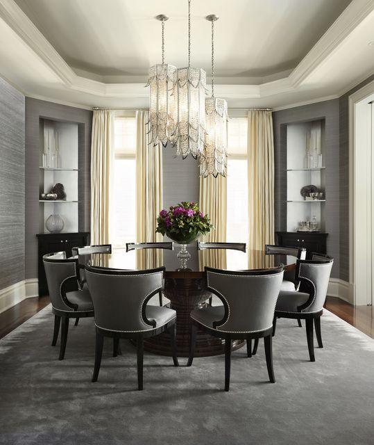 Okrągły stół z blatem pokrytym szkłem. Drewniane i masywne stoły zwykle bazują na naturalnych kolorach i nie zawierają dodatkowych urozmaiceń, dlatego szkło będzie tutaj elementem wyróżniającym. Szare krzesła w tym samym modelu dodają całości kunsztu, którego będziecie oczekiwać. Podobnie zresztą jak oświetlenie sufitowe najwyższej klasy. Na całe szczęście nie brakło również kwiatów, a te zawsze sobie cenimy, szczególnie tak piękne. #dom #jadalnia ##okrągły ##stół