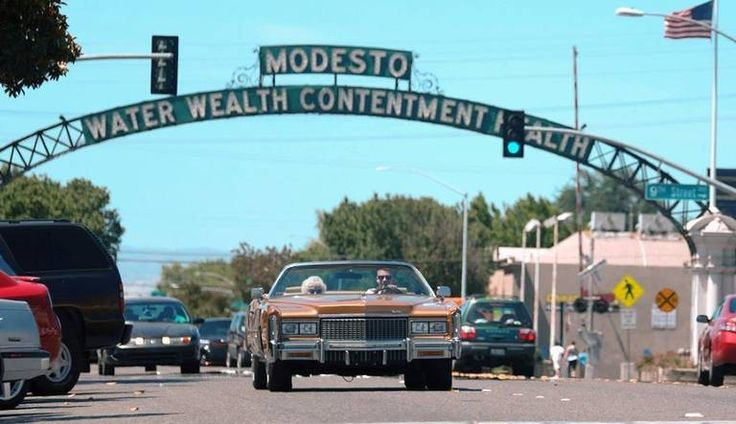 """Hip-hop artist Macklemore and his grandmother, Helen Schott, shown driving near the Modesto Arch on I street in a still from his new music video """"Glorious."""" The city of Modesto in California is the backdrop for the video, which shows Macklemore spending the day with his grandmother at various locations around town. It was shot over a few days over mid-June."""