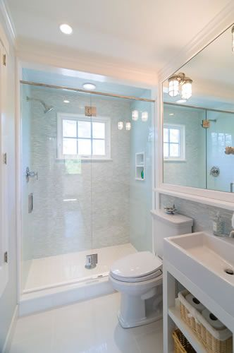 Small bathroom that looks big with white decor and large glass shower