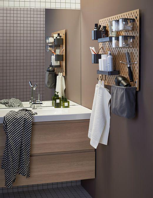 En SKÅDIS opbevaringstavle af træ monteret ved siden af en vask i et badeværelse med tilbehør til opbevaring af tandbørster, håndklæder og andre toiletartikler.